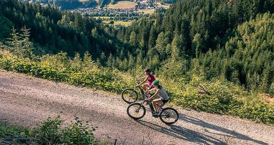 zwei-frauen-fahren-mit-dem-e-mountaibike-einen-steilen-forstweg-hinauf