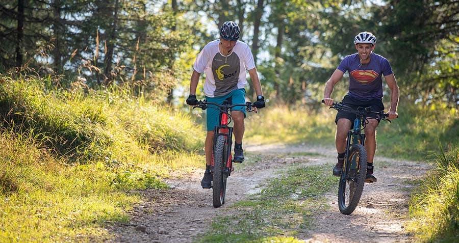 zwei-maenner-fahren-mit-dem-e-bike-ueber-einen-forstweg