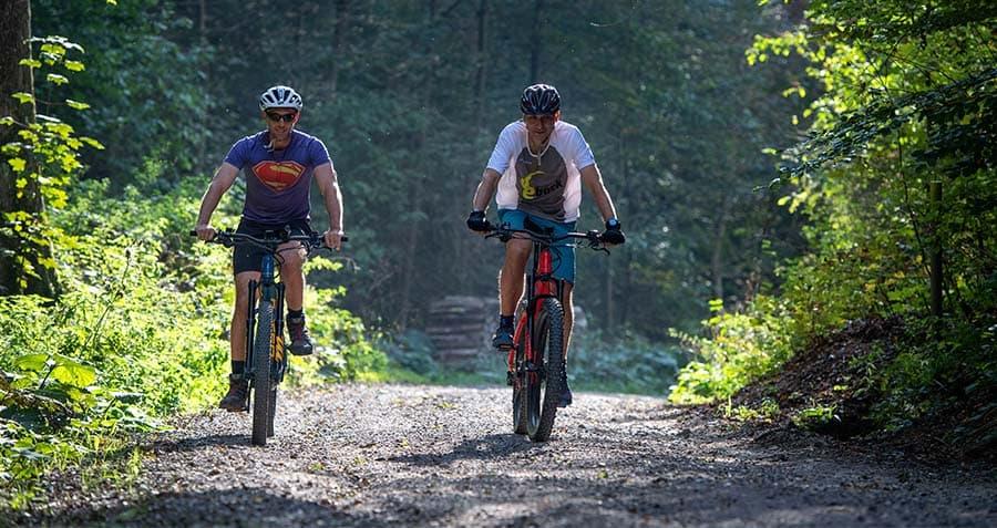 zwei-maenner-fahren-mit-dem-e-bike-ueber-einen-waldweg