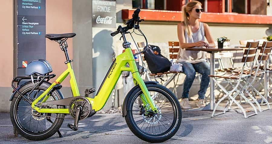 e-bike-faltrad-von-flyer-in-gruen-mit-dame-am-bistrotisch