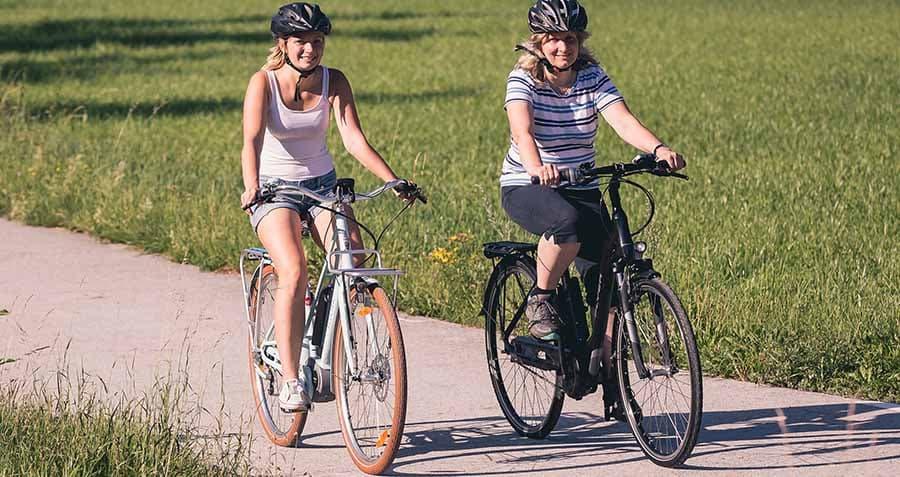 zwei-frauen-fahren-mit-dem-e-bike-entlang-am-radweg